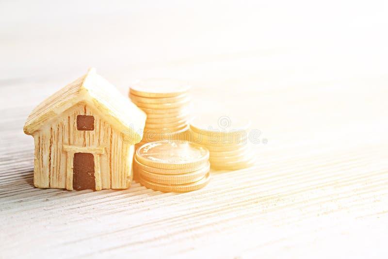 Bringen Sie Modell und Münzen auf Schreibtischtabelle mit Kopienraum unter stockbilder