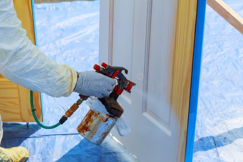 Bringen Sie Reparaturfarbe die Holztür in der weißen Farbe mit einem Spray unter lizenzfreie stockfotografie