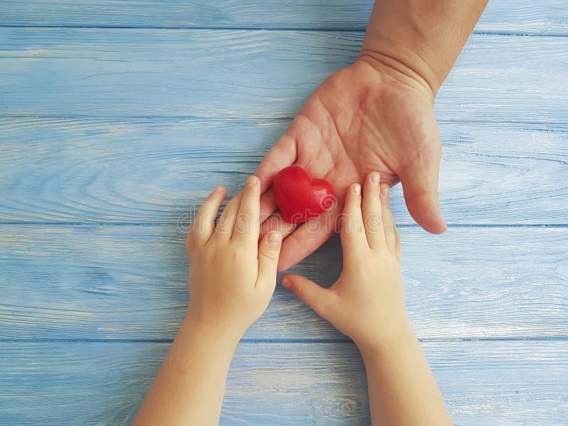 Bringen Sie ` s Tageshände der Vati und Kind hervor, die grüßender kreativer Holding dankbares Herz auf einem blauen hölzernen Hi stockfotos
