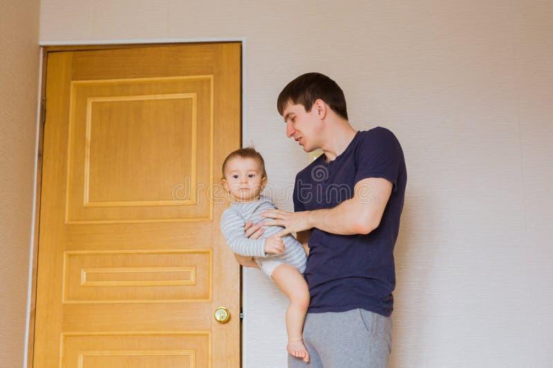 Bringen Sie ` s Tageskonzept - glücklicher Familienvater und Babykindersohn zuhause hervor stockfoto