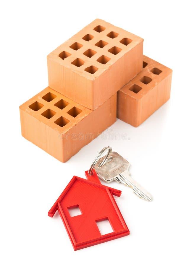 Bringen Sie Türschlüssel mit rotem Hausschlüsselanhängeranhänger und -ziegelsteinen unter lizenzfreie stockfotos