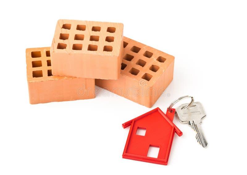 Bringen Sie Türschlüssel mit rotem Hausschlüsselanhängeranhänger und -ziegelsteinen unter lizenzfreies stockbild