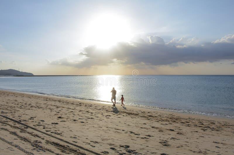 Bringen Sie und der Junge hervor, der auf den Strand geht stockfoto