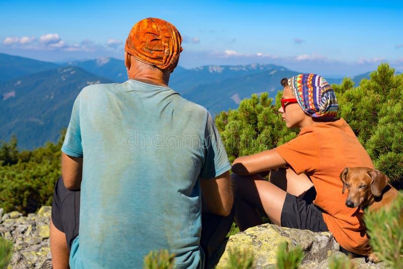 Bringen Sie und sein jugendlicher Sohn mit lustigem Hund in den Bergen hervor stockfoto
