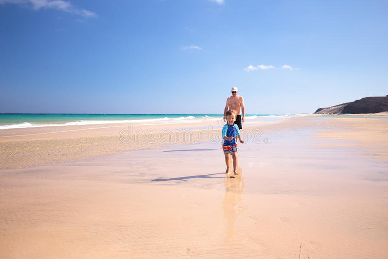 Bringen Sie und sein kleiner Sohn hervor, der Spaß und Betrieb auf dem Strand hat lizenzfreie stockfotografie
