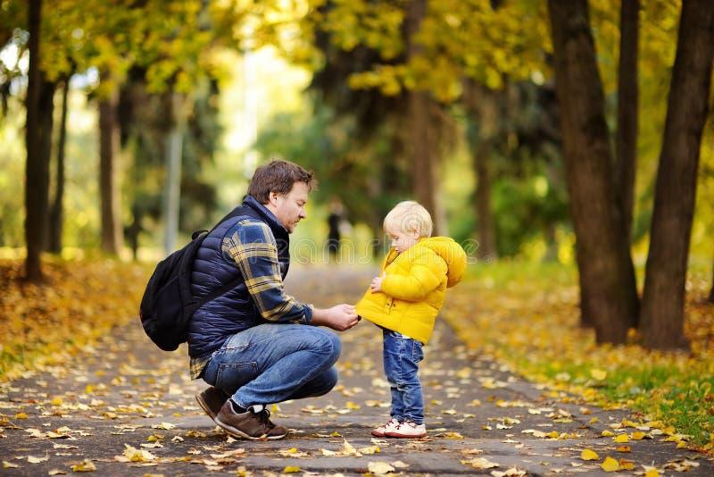 Bringen Sie und sein Kleinkindsohn hervor, der in Herbstpark geht stockfoto