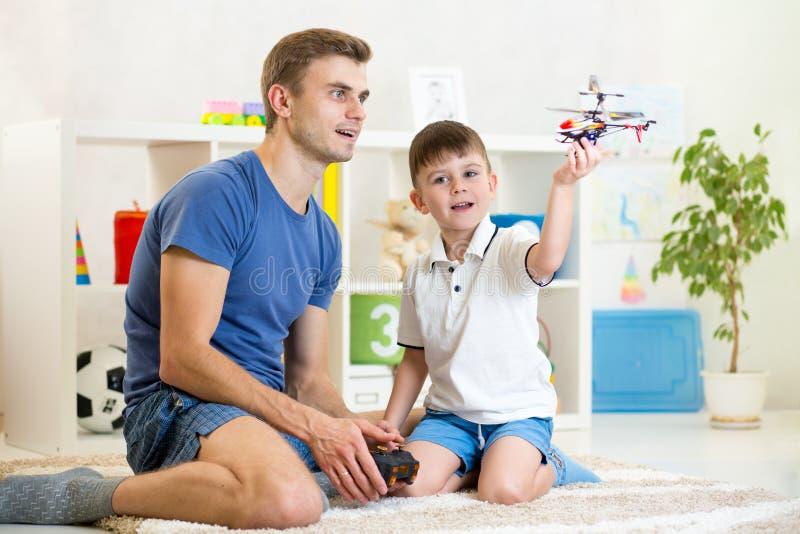 Bringen Sie und sein Sohnspiel mit RC-Hubschrauberspielzeug hervor stockfotos