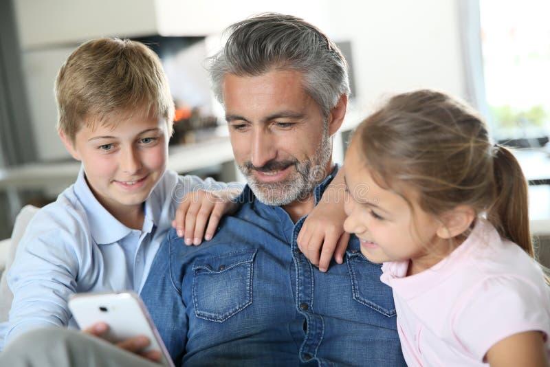 Bringen Sie und seine zwei Kinder hervor, die auf Smartphone spielen lizenzfreie stockbilder