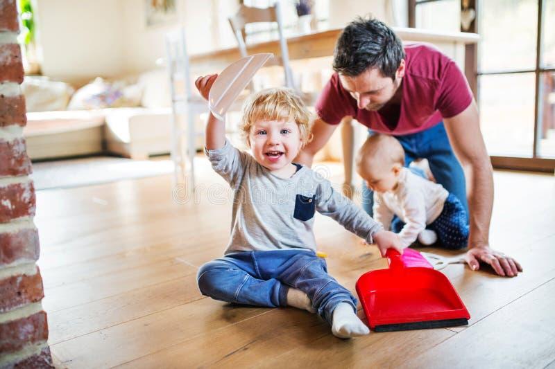 Bringen Sie und zwei Kleinkinder mit Bürste und Müllschippe hervor stockbild