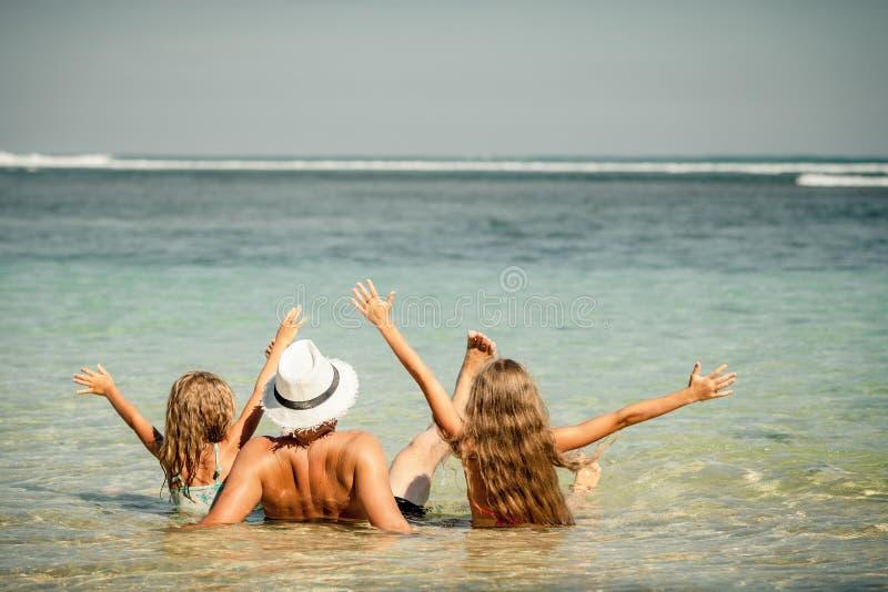 Bringen Sie und zwei Töchter hervor, die am Strand sitzen lizenzfreie stockbilder