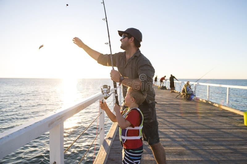 Bringen Sie unterrichtenden kleinen jungen Sohn hervor, um ein Fischer zu sein und auf Seedockdamm zusammen fischen genießend und stockbilder