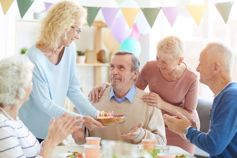 Bringing birthday cake with candles. Smiling attractive women in glasses bringing birthday cake with candles for birthday men at house dinner party royalty free stock images