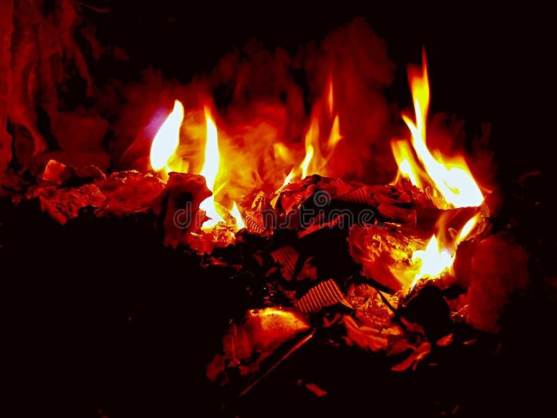Brinnande avskräde för röd brand med svart bakgrund arkivbild