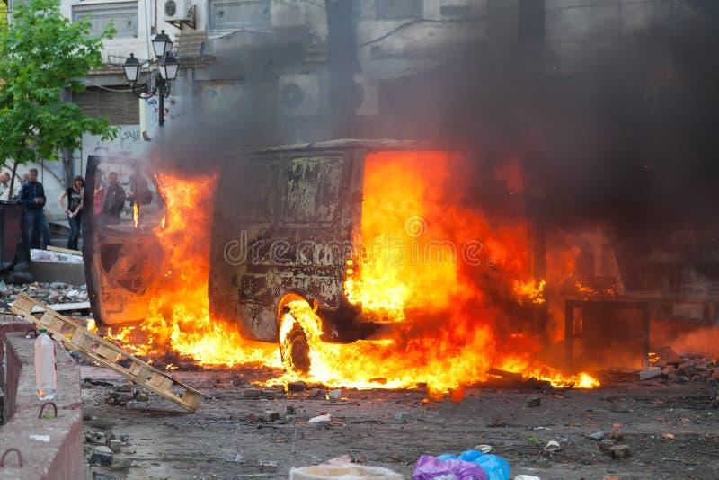 Brinnande bil i mitten av staden under oro fotografering för bildbyråer