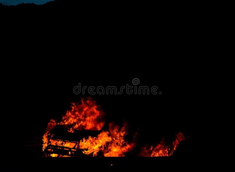 Brinnande bil på vägen på natten, en ändelse för tragisk olycka med royaltyfria foton