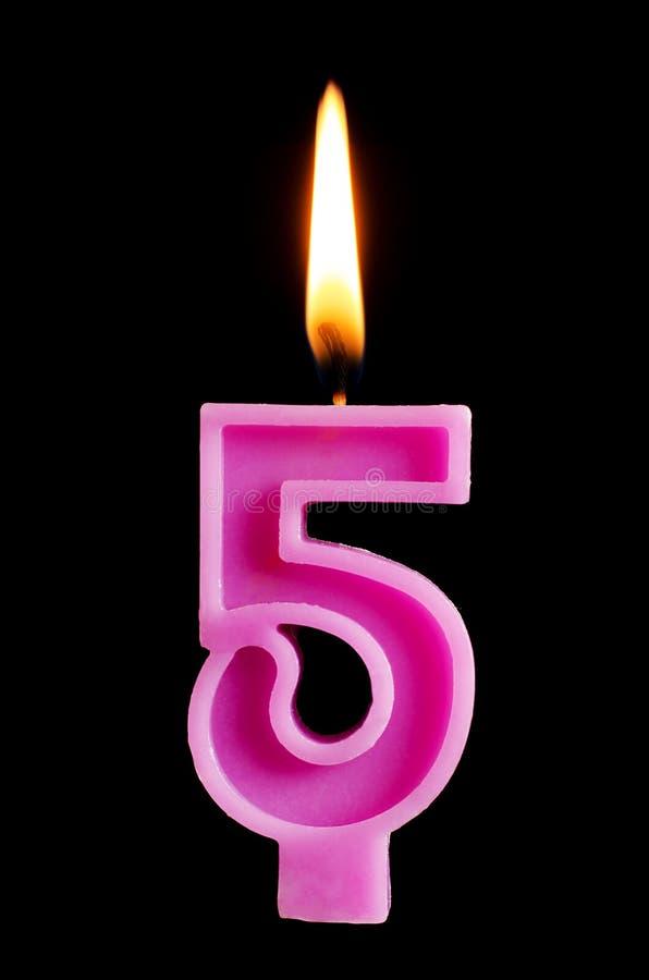 Brinnande födelsedagstearinljus i form av 5 fem diagram för den isolerade kakan på svart bakgrund Begreppet av att fira en födels royaltyfria bilder