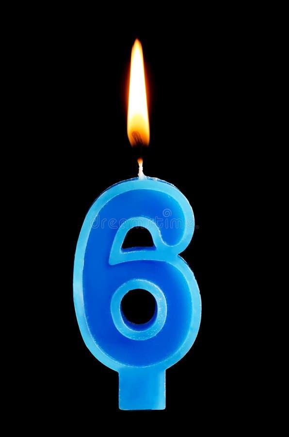 Brinnande födelsedagstearinljus i form av 6 sex diagram för den isolerade kakan på svart bakgrund Begreppet av att fira en födels royaltyfri bild
