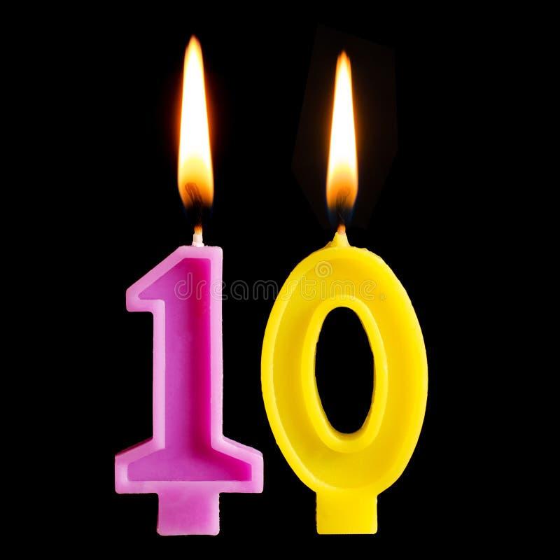 Brinnande födelsedagstearinljus i form av 10 tio diagram för den isolerade kakan på svart bakgrund Begreppet av att fira en birth arkivbild
