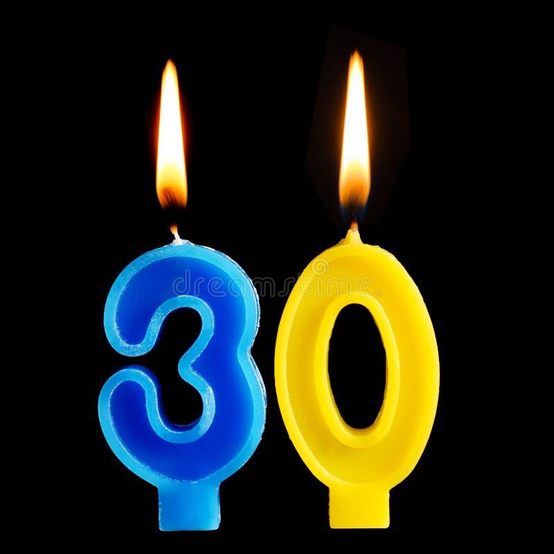 Brinnande födelsedagstearinljus i form av 30 trettio diagram för den isolerade kakan på svart bakgrund Begreppet av att fira en b arkivfoto