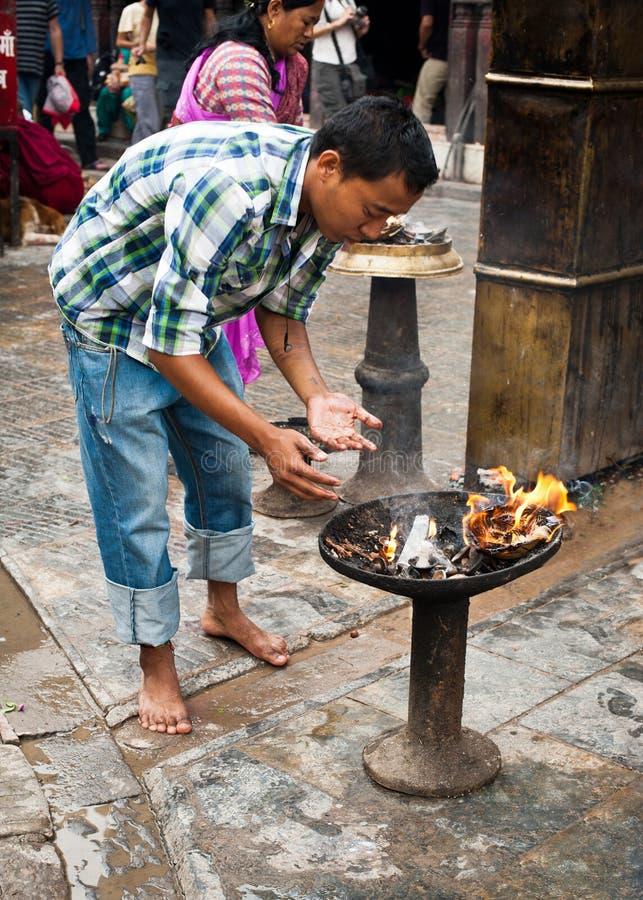 Brinnande offerings för Nepaliman på religiös ceremoni på Swayambhunath Stupa Nepal Kathmandu royaltyfria bilder