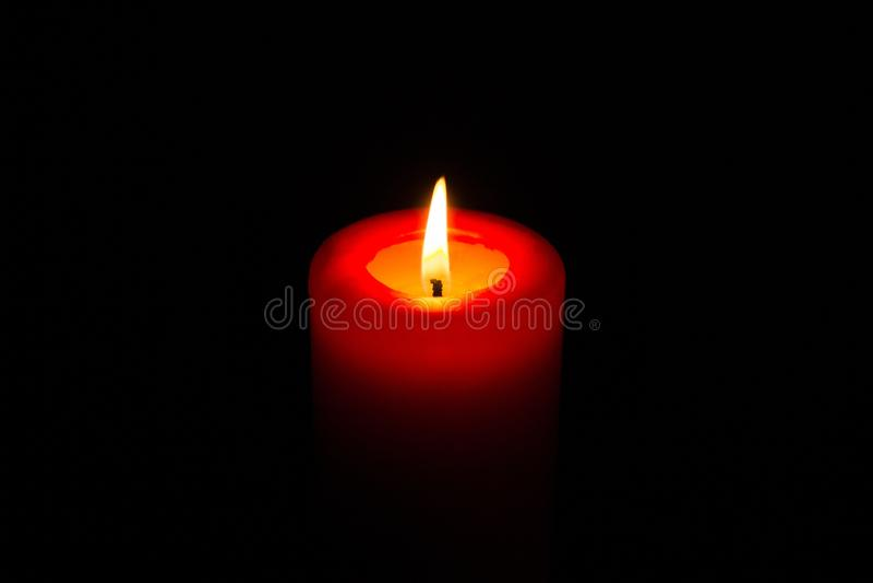 Brinnande röd stearinljus i mörkret royaltyfria bilder