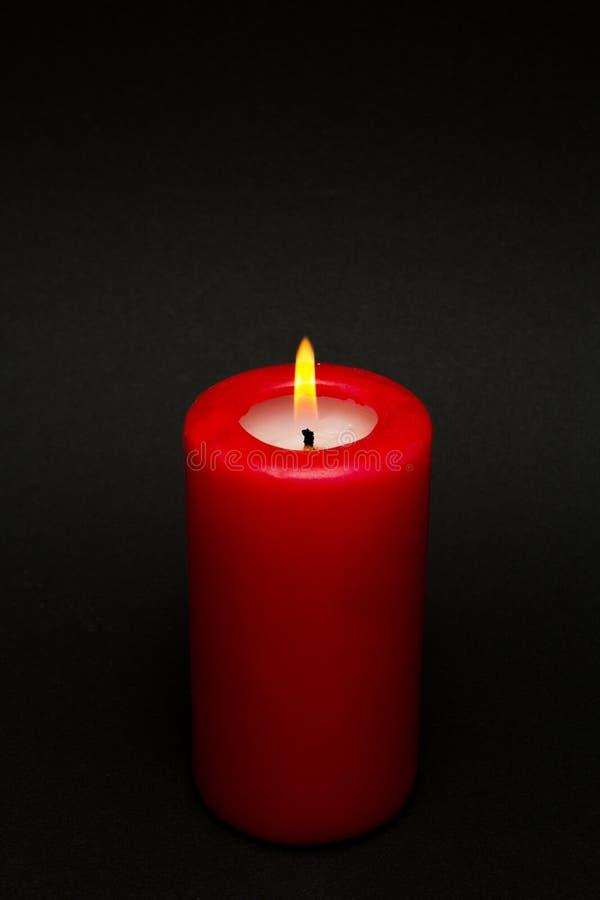 Brinnande röd stearinljus på en svart bakgrund arkivfoto