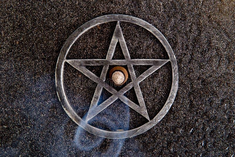 Brinnande rökelse i mitt av grå färger belägger med metall pentagram kritiserar på backg royaltyfria bilder