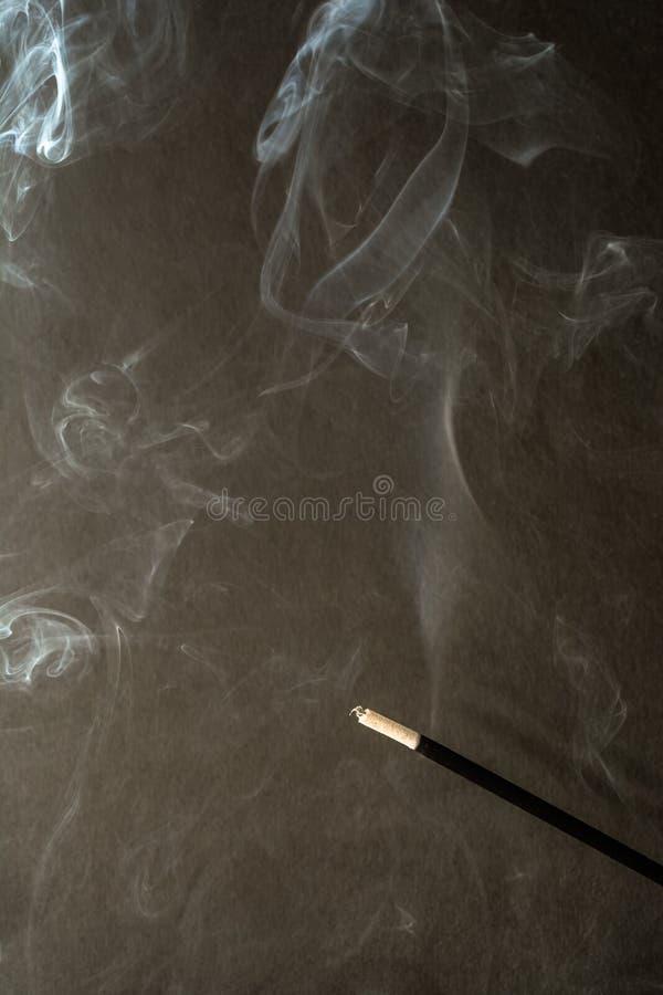 Brinnande rökelse klibbar med rök på mörk bakgrund arkivbilder