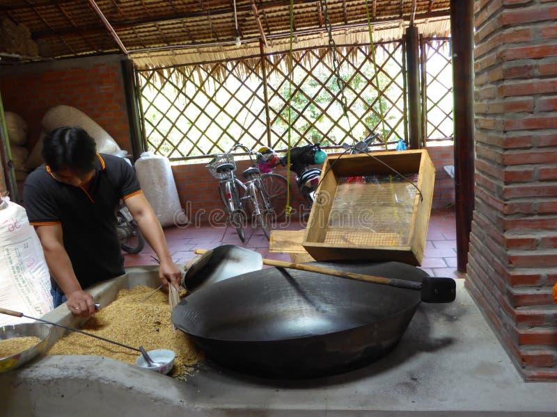 Brinnande skal för vietnamesisk man för framställning av rostade risgodisar arkivfoton