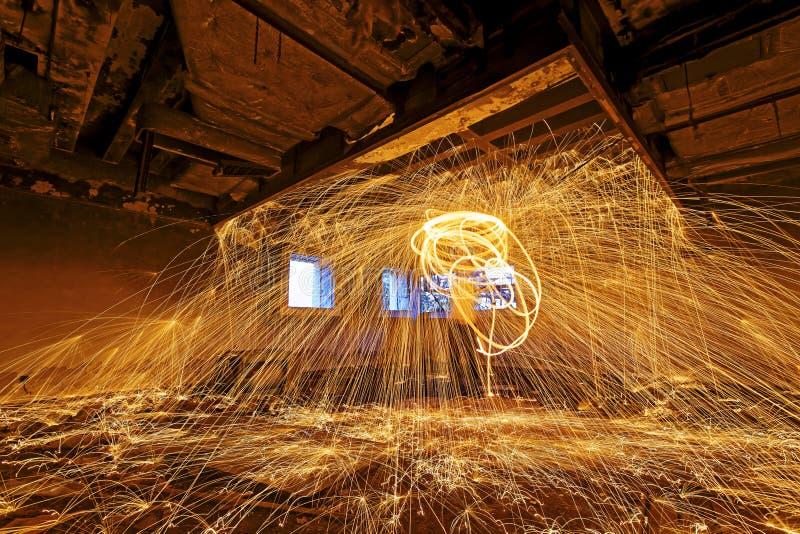Brinnande snurr för stålull Duschar av glödande gnistor från snurrandet arkivbilder