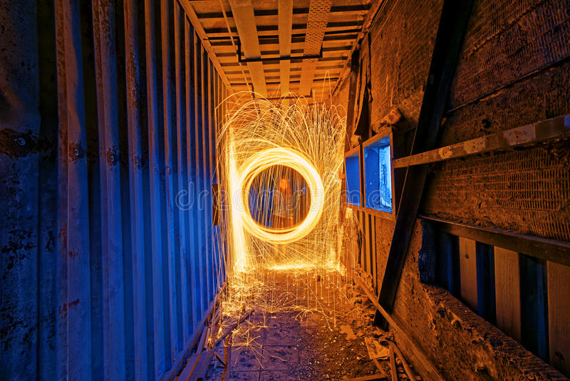 Brinnande snurr för stålull Duschar av glödande gnistor från snurrandet arkivfoton