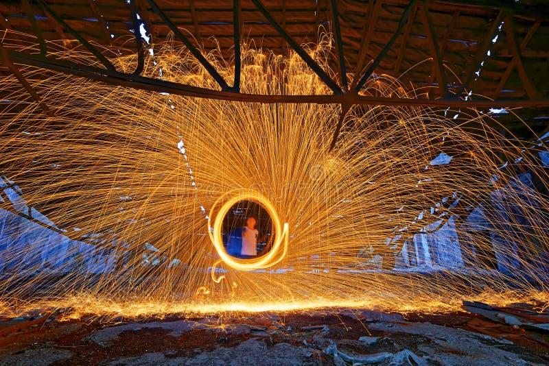 Brinnande snurr för stålull Duschar av glödande gnistor från snurrandet royaltyfria foton