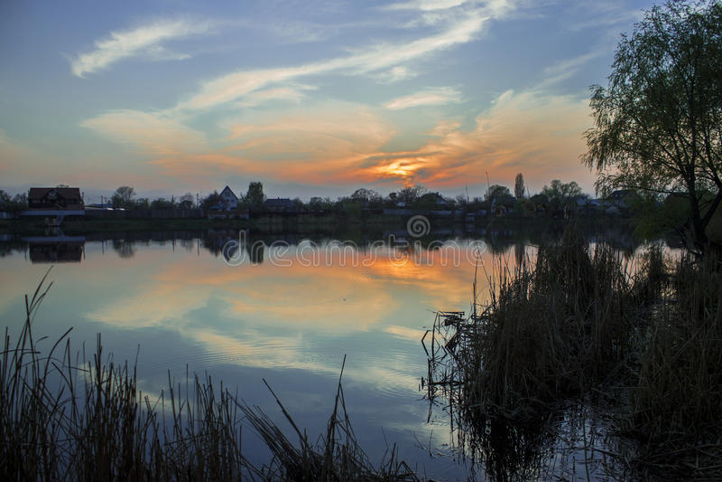 Brinnande solnedgång över byn royaltyfri bild
