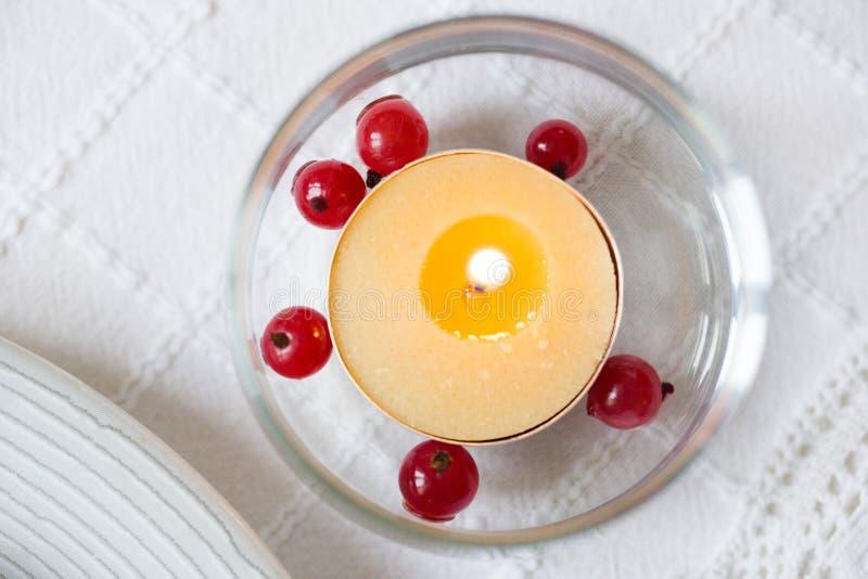 Brinnande stearinljus i exponeringsglas med röda bär - röd vinbär royaltyfria foton