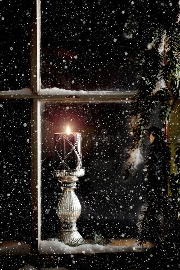 Brinnande stearinljus i fönster fotografering för bildbyråer