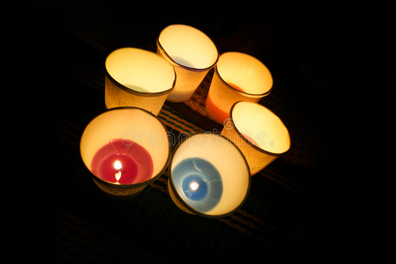brinnande stearinljus i pappers- koppar royaltyfria bilder