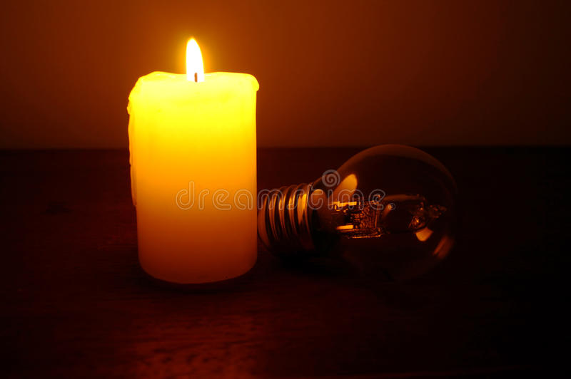 Brinnande stearinljus och lampa på skrivbordet arkivfoto