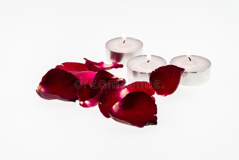 Brinnande stearinljus och röd ros fotografering för bildbyråer