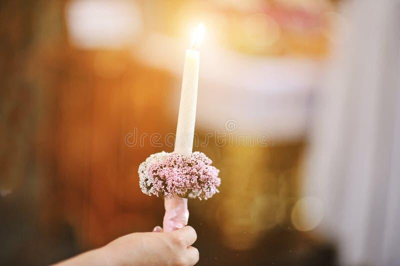Brinnande stearinljus på handen av bruden på bröllopceremoni på kyrkan royaltyfri bild
