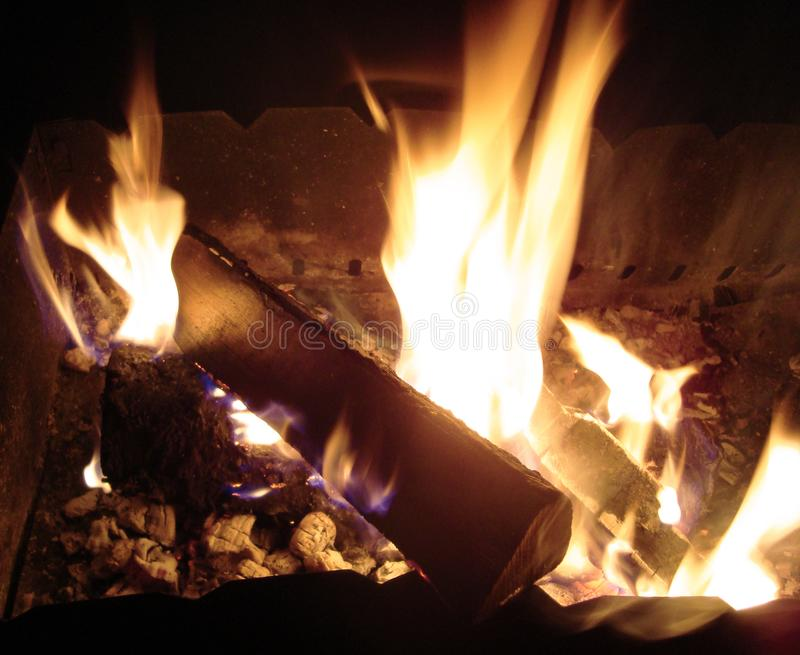 Brinnande trä i fyrpanna arkivfoto