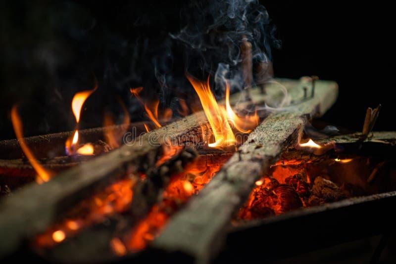 Brinnande trä på ett galler mycket av kol arkivfoton