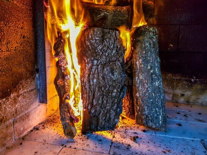 Brinnande vedtr? i spiscloseupen, de gl?dande journalerna, branden och flammorna fotografering för bildbyråer