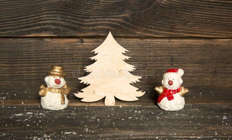 Brinque bonecos de neve e a árvore de Natal de madeira em um backgroun de madeira escuro imagens de stock