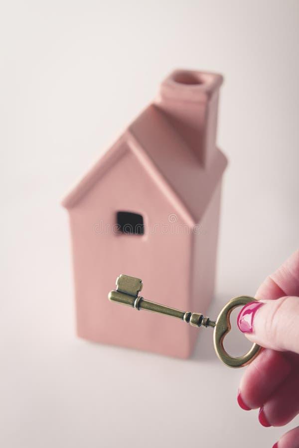 Brinque a casa cor-de-rosa com a mão que guarda chave na parte dianteira fotos de stock royalty free