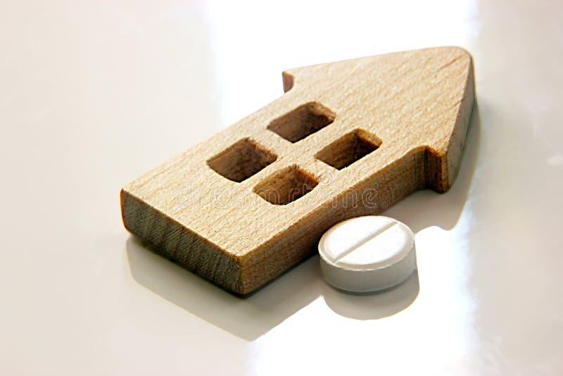 Brinque a casa e o comprimido de madeira em um fundo claro, o conceito de hospitais da construção fotografia de stock royalty free