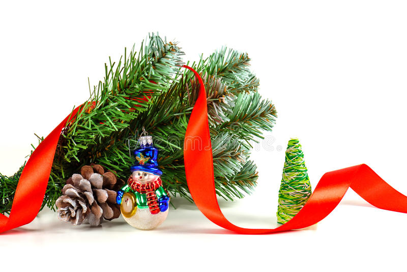 Brinque o boneco de neve sob um ramo de uma árvore de Natal artificial com o cone imagem de stock