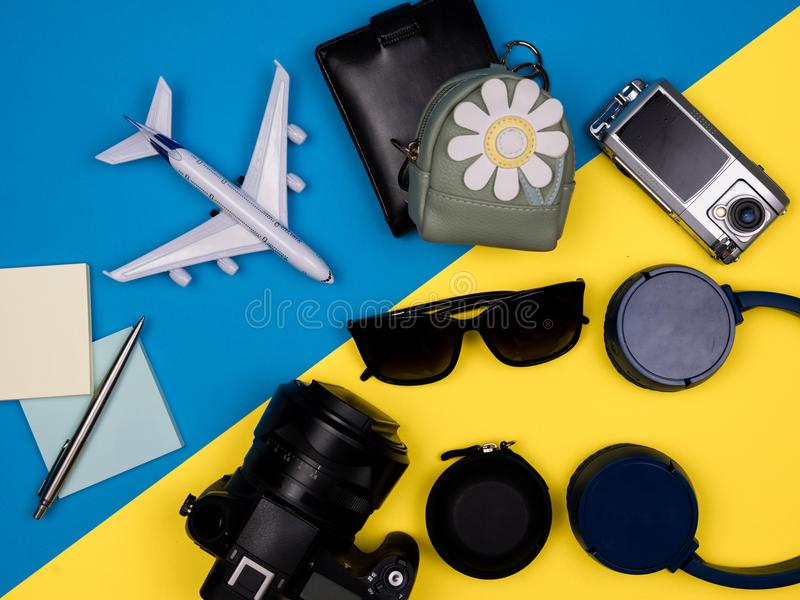 Brinque o plano, a câmera, os óculos de sol, os fones de ouvido, a carteira, a câmera da ação e a trouxa foto de stock