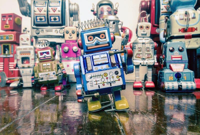 Brinquedo azul pequeno do robô do baterista em um assoalho de madeira com reflexão imagens de stock