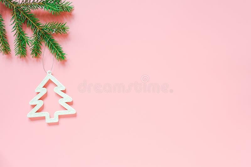 Brinquedo da árvore da decoração do White Christmas no ramo do abeto no fundo cor-de-rosa com espaço da cópia Feliz Natal do conc imagens de stock