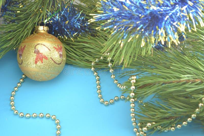 Brinquedo da árvore: dourado, amarelo, bola, Natal e ano novo em um ramo do pinho decorado com grânulos do ouro em um fundo azul fotos de stock royalty free